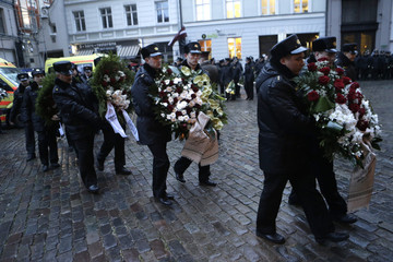 Police officers hold wreaths as they attend the funeral ceremony of the three firefighters killed during rescue works of a collapsed supermarket in Riga