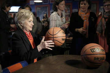 U.S. Democratic presidential candidate Hillary Clinton bounces a basketball on a table during a campaign stop at Varsity Pizza in Syracuse