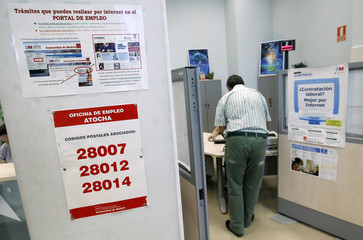A man speaks to a staff member at a government-run employment office in Madrid