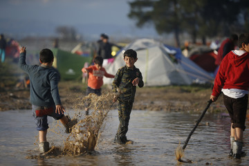 Young boys play in a muddy puddle in a makeshift camp for migrants waiting to cross the Greek-Macedonian border near Idomeni