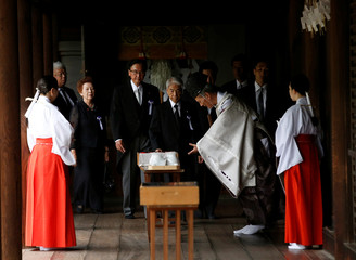A Shinto priest suggests a group of lawmakers to sip a sake as a ritual after the lawmakers offered prayers at Yasukuni Shrine on the anniversary of Japan's surrender in World War Two in Tokyo