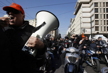 Public transport employees shout slogans as they ride on motorcycles during a protest in Athens