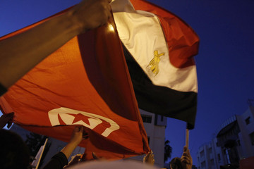 Tunisian and Egyptians living in Tunis wave an Egyptian and Tunisian flag celebrating the resignation of Egypt's President Hosni Mubarak in front of the Egyptian Embassy in Tunis