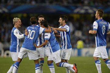 Real Sociedad players celebrate a goal against Olympique Lyon during their Champions League play-off soccer match at Anoeta stadium in San Sebastian