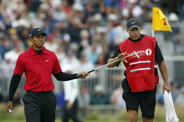 Tiger Woods of the U.S. hands his putter to his caddie Steve Williams as he walks off the second green during the final round of the British Open golf championship on the Old Course in St. Andrews