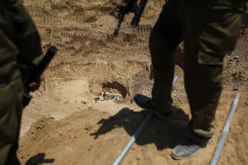 Israeli soldiers stand above a part of a tunnel exposed by the Israeli military near the Israel-Gaza border