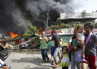 Residents evacuate into the streets as houses burn in a residential district after a clash between government soldiers and Muslim rebels from the MNLF in Zamboanga city