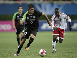 Lewis of Trinidad and Tobago chases Arce of Mexico as he runs with the ball during their men's first round group A soccer match at the Pan American Games in Guadalajara