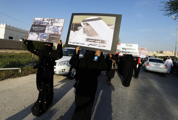 Mourners, including family members of policeman Ali, hold posters with pictures of UAE police officer Shihhi, during a protest after Ali's funeral procession in Hananya