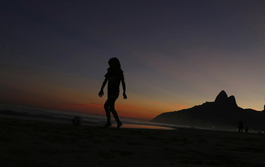 A girl walks along the shore while she plays with a ball at ipanema beach, as the Dois Irmaos (Two brothers) peaks are seen in the background, during sunset in Rio de Janeiro