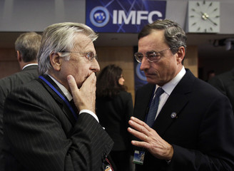 ECB President Trichet talk to Italy's Central Bank Governor Draghi at the IMFC meeting during the annual IMF-World Bank meetings in Washington