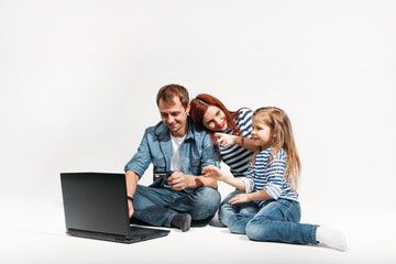 Happy family Father, mother and child lying on the floor with laptop and credit card on white background isolated