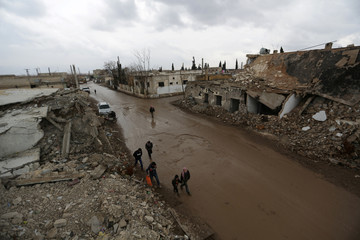 People walk past damaged buildings in al-Rai town