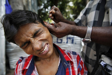 """A customer reacts as an """"ear cleaner"""" works on his ear in Mumbai"""