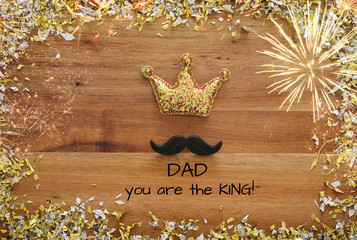 Top view image of funny mustache and glitter crown. Father's day concept
