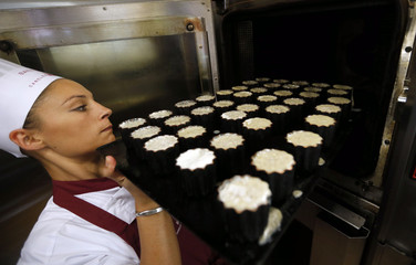 A pastry chef puts a tray of batter into an oven to make caneles, a small French pastry, at the Maison Baillardran cake shop in Bordeaux