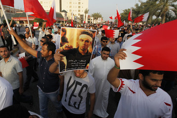 A protester holding a poster of martyr Ali Jasim, who died during the 2011 uprising in Bahrain, participates in an anti-government rally in Budaiya
