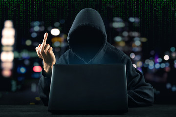 Hacker in front of his computer show middle finger. Dark face