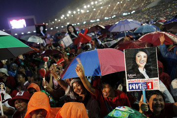 Red shirt supporters brave heavy rains to listen to Yingluck Shinawatra as she addresses the last big pre-election rally for her Puea Thai (For Thais) party in Bangkok