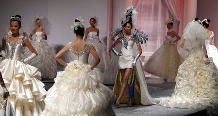 Models present creations from a wedding dress collection by designer Tsai Meiyue at China Fashion Week in Beijing