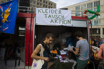 Campaigners exchange second hand clothes during a protest outside a store of clothing retailer Primark before its opening in Berlin