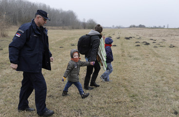 Serbian border policeman escorts Kosovars, who were trying to cross the border to Hungary near the town of Subotica, near the Serbian-Hungarian border