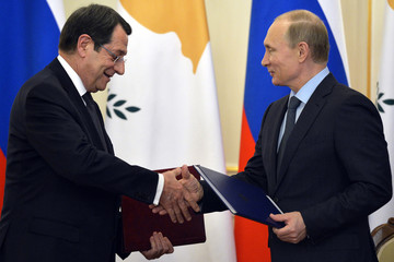 Russian President Vladimir Putin and Cyprus President Nicos Anastasiades shake hands after signing documents at the Novo-Ogaryovo state residence outside Moscow