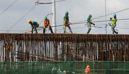 Labourers work at a construction site of a new expressway in Manila
