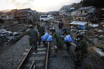 Members of Japan's Self Defense force carry the body of a victim found in ruins of destroyed residential part of Kesennuma