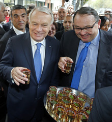 French Prime Minister Ayrault drinks a tea with French Socialist Party deputy and candidate for the 2014 Marseille local elections Mennucci in front of a Tunisian pastry shop during a one day visit in Marseille