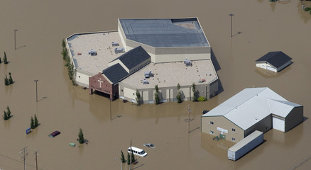 A church is surrounded by flood waters in High River