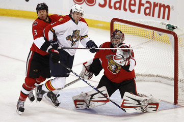 Senators' goalie Anderson makes a save as Senators' Methot hits Panthers' Huberdeau during their NHL hockey game in Ottawa