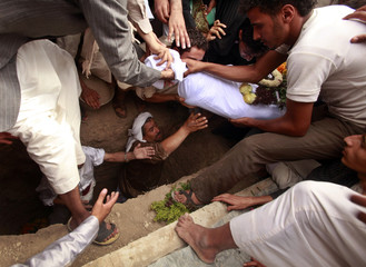Mourners bury the body of Hassan al-Hora during his funeral at a cemetery in Sanaa