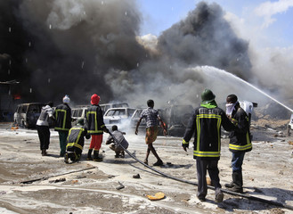 Firefighters work to extinguish an accidental explosion at a petrol storage facility within the former U.S. embassy's residential compound, in Mogadishu