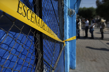 A police cordon is seen as journalists wait their turn to take pictures, at a drug and alcohol rehabilitation centre that was attacked by gunmen in Torreon