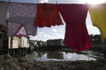Laundry hangs on a clothesline in front of houses at a lake dwelling in Recife