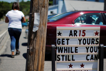"A pedestrian walks past a sign reading ""AR15 Get Yours While You Still Can"" outside the IDC Firearms gun shop in Clinton"