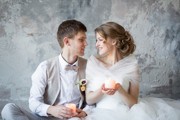 Portrait of a wedding couple with candles in a loft room