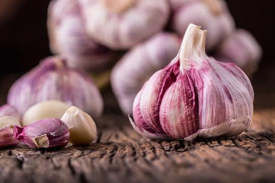 Garlic. Fresh garlic bulbs on old wooden board. Red violet garlic.
