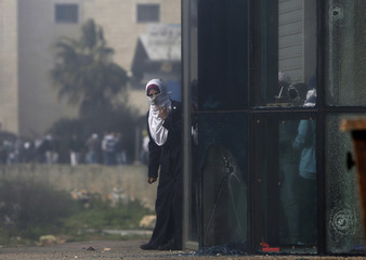 A Palestinian protester holds stones as she stands near broken glass during clashes with Israeli soldiers near Ramallah