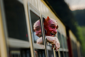 Man with devil make-up looks out of HSB light railway carriage as he travels through the Harz mountains