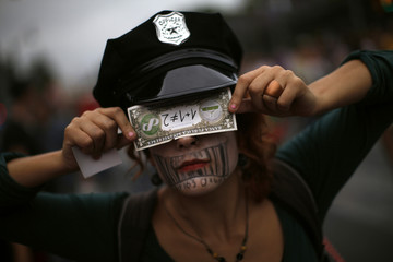A demonstrator covers her eyes with a mock currency note during a demonstration in Malaga