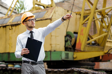 Engineer builder in a helmet holds drawings and shows by hand at construction site