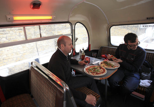 Diners eat pizza on the top deck of the Big Red Pizza Bus in Deptford, south east London