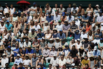 Spectators sheild under umbrella as others sit in the sunshine at the Wimbledon Tennis Championships in London