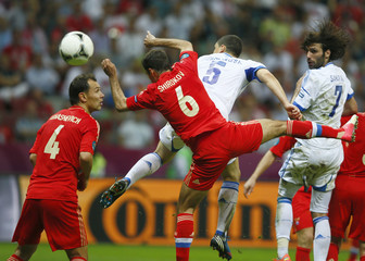 Russia's Ignashevich and Shirokov jump for a header with Greece's Papadopoulos and Samaras during their Group A Euro 2012 soccer match at the National stadium in Warsaw
