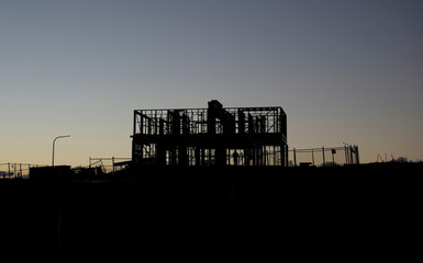 Labourer stands in the wooden frame of a house under construction in Sydney