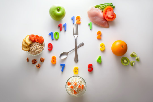 Clock made of spoon and fork. Schedule of proper nutrition. Oatmeal for breakfast, fruit for snack, meat with vegetables for dinner, cottage cheese for dinner