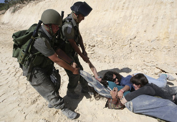 A foreign activist is dragged by Israeli border police officers after blocking a bulldozer at a construction site in al Wallaje