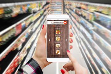 Woman in supermarket using smartphone for food recepies